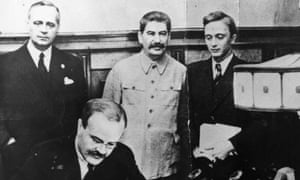 23rd August 1939: Vyacheslav Mikhaylovich Molotov, Russian Foreign Minister, signs the non-aggression pact negotiated between Soviet Russia and Germany. Standing behind him is his German counterpart Joachim von Ribbentrop (left), and Joseph Stalin (centre).