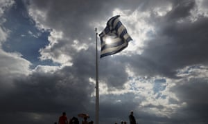Tourists stand beneath a Greek flag fluttering against  the sun at the ancient Acropolis hill , in Athens, on Monday June 22, 2015