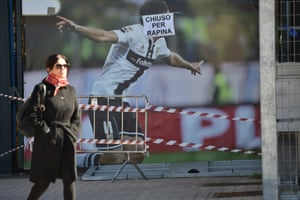 A woman walks past a banner which translates as 'closed for robbery' stuck on to a poster at  the entrance of Ennio Tardini Stadium in Parma.