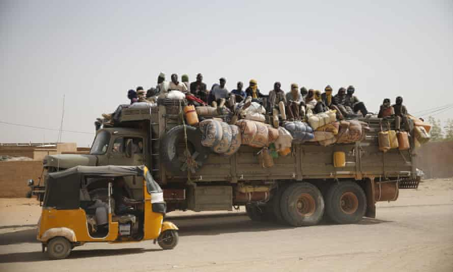 Migrants sit on their belongings in the back of a truck as it is driven through a dusty road in the desert town of Agadez, Niger