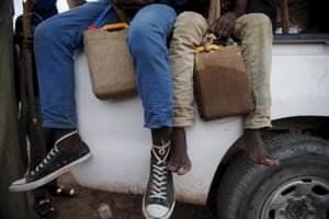Migrants hold containers of water wrapped with wet sacks as they sit in the back of a truck in Agadez.