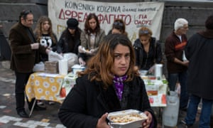 A woman receives a portion of food at a soup kitchen in Athens.