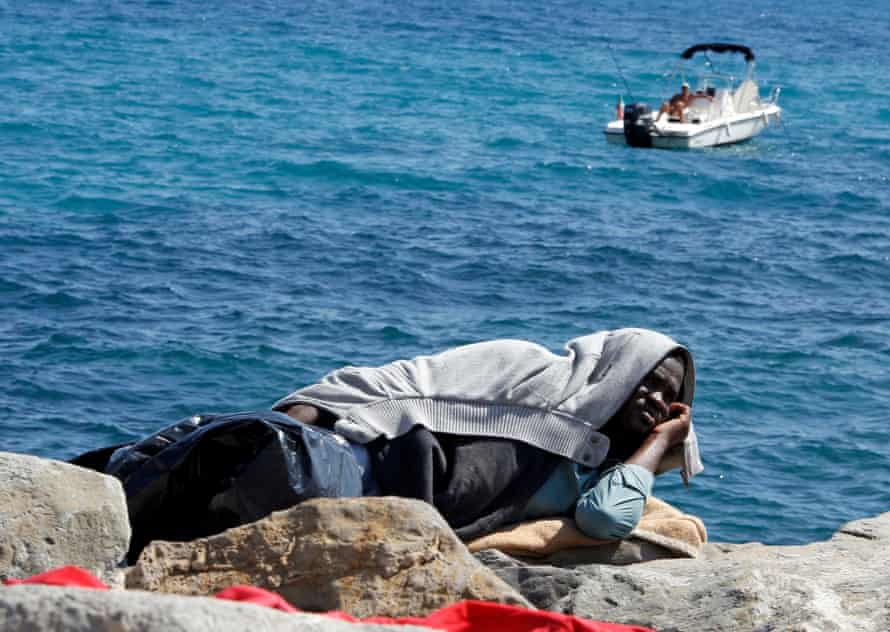 A man relaxes while fishing from his boat while a migrant rests on the seawall at the Saint Ludovic border crossing between Italy and France.