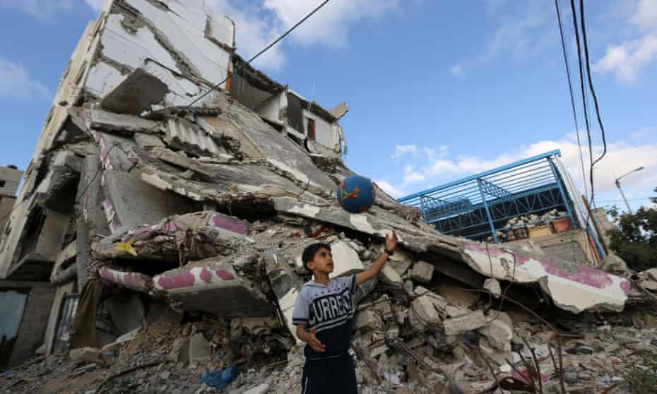 A Palestinian boy plays football outside the remains of his house in Gaza City that was destroyed during the summer 2014 war.