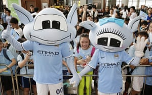 The Manchester City mascots Moonchester and Moonbeam wave at fans at Hong Kong airport. Two aliens who come from the planet 'Blue Moon'
