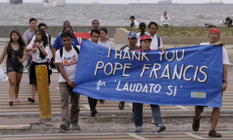 Environmental activists march towards a Roman Catholic church