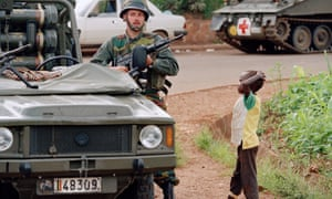 A Belgian soldier from a UN convoy with a Rwandan boy  in Kigali, Rwanda, in April  1994