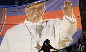 Fans hold a banner with a photo of Pope Francis at a football match in Argentina.