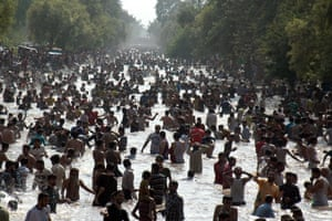 People cool off in a canal in Lahore
