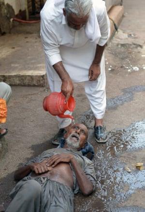 A heatstroke victim is assisted in a Karachi market