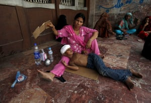 A woman fans her son while waiting for a medical checkup in Karachi