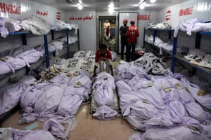 Rescue workers move the bodies of the victims of heatwave at a mortuary in Karachi