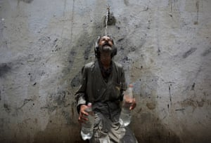 A man cools off under a public tap in Karachi