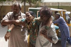 Family members take a woman suffering from heatstroke to hospital