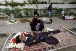 A fatehr tries to cool down his son, while waiting their turn for a medical checkup