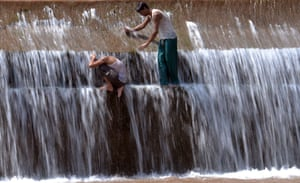 Youths cool themselves off in a river on the outskirts of Islamabad