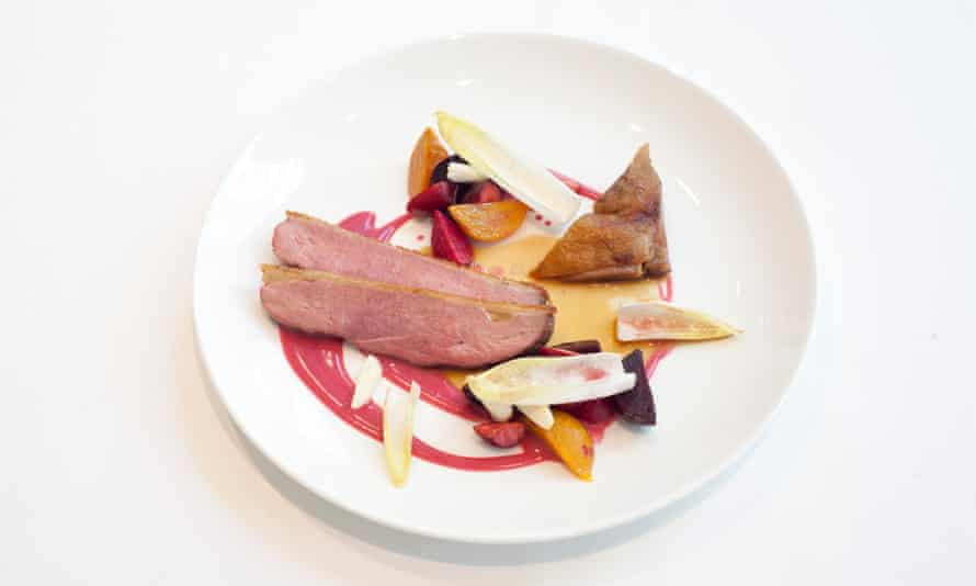 Slices of duck breast and boned-out confit leg on a round plate