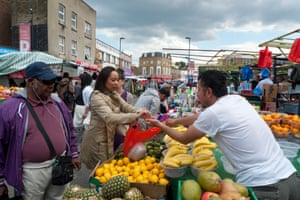 A woman buys fruit at Ridley Road Market. Figures show that market and convenience store purchases have fallen by 13%.