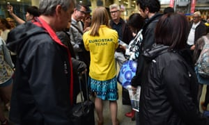 A member if the Eurostar Team talk to passengers queuing at the Eurostar terminal at St Pancras station