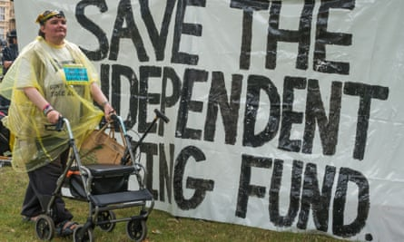 Paula Peters of DPAC walking in front of a large banner 'Save The Independent Living Fund' during the occupation of the grass outside Westminster Abbey in June 2014.