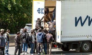 Migrants climb into the back of a lorry in Calais, France