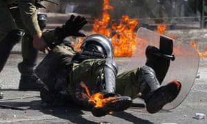 A riot police officer is hit by a petrol bomb thrown by protesters during a nationwide general strike in Athens.