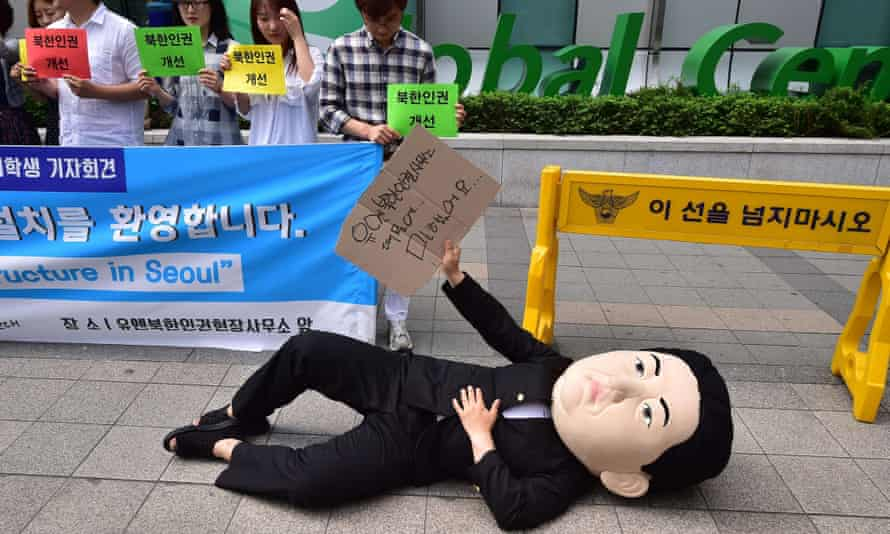A South Korean activist wearing a mask depicting North Korean leader Kim Jong-un lies on a street during a rally to welcome the opening of the UN Human Rights office in Seoul.