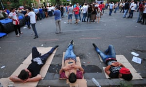 Demonstrators lie on the street in Yerevan. Hundreds of protesters defied police, ignoring a call to disperse and digging in for a new day of action to draw attention to electricity price hikes and police violence