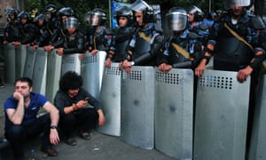 Demonstrators sit on the pavement in front of a line of riot police in the capital. The protests have entered their fifth day, with an estimated 6,000 taking to the streets 23 June