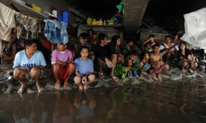 Could a global tax system help stem the rising tide of inequality? A group of Philippine farm workers seek shelter from rains and floodwaters north of Manila, August 2012.