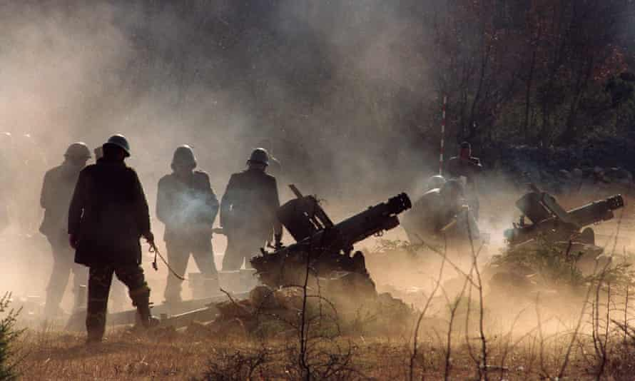 Serbian soldiers firing howitzers during the Bosnia conflict.