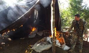 A Senad soldier sets light to a trafficker's tent.