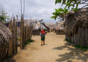 A Kuna woman walks past traditional houses