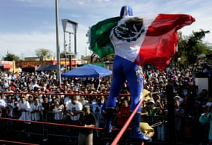 Lucha Libre Star Blue Demon Jr waves the Mexican flag after winning a wrestling match in Miami.