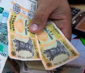 An employee displays Moldovan leu banknotes.