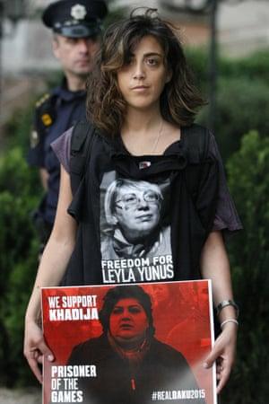 A protester holds a poster showing Azerbaijami jailed journalist Khadija Ismayilova