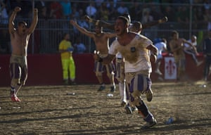 Santo Spirito Bianchi players celebrate winning the final of the Calcio Storico Fiorentino. The winning team is presented with a Chianina cow, one of the oldest breeds of cow in existence.