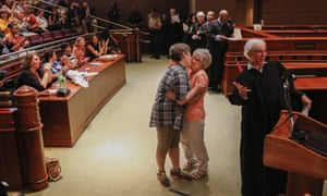 Fulton County state court Judge Jane Morrison celebrates as Sheila Woods kisses her newly married wife Paula Bosworth during a mass wedding ceremony in Atlanta, Georgia