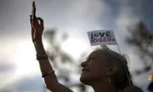 A woman takes a photo at a celebration rally in West Hollywood, California