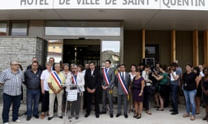 Local councillors hold a minute's silence outside Saint-Quentin-Fallavier town hall on Saturday.