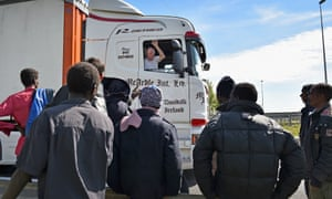 Migrants attempting to board lorries at Calais.