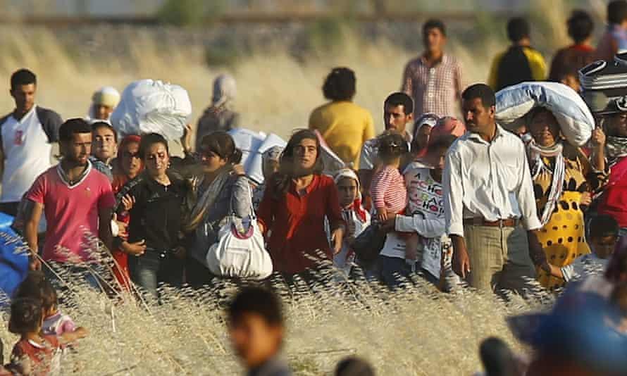 Syrian Kurds fleeing the fighting in Kobani walk to  the Turkish border on Friday.
