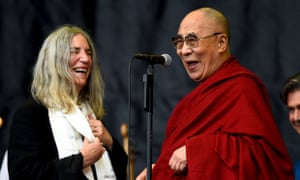 Patti Smith (L) shares a light moment with the Dalai Lama as she performs on the Pyramid stage at Worthy Farm in Somerset during the Glastonbury