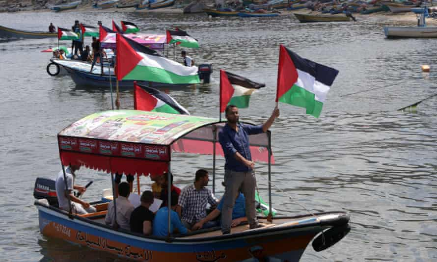 Palestinians hold their national flag as they ride boats during a rally to show support for activists on the Freedom Flotilla III at the seaport of Gaza City on 24 June 2015.