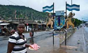 People walk past a city sign in Freetown in August 2014. Sierra Leone has more confirmed cases of Ebola than any other country.