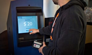 """A customer uses the world's first ever permanent bitcoin ATM unveiled at a coffee shop in Vancouver, British Columbia 29 October, 2013. <a href=""""http://www.coinfox.info/news/2256-greek-bitcoin-enthusiasts-installed-first-bitcoin-atm-in-athens"""">A similar model was launched in Athens on 22 June, 2015</a>."""