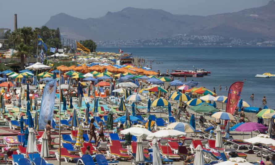 Tourists relax on the beach in Kos, Greece