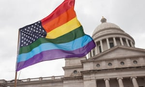 "A rainbow flag flies over the crowd during a press conference by the Human Rights Campaign on the steps of the Arkansas State Capital in Little Rock following Gov. Asa Hutchinson's comments on House Bill 1228, a bill passed which prohibits state and local governments from infringing on a person's religious beliefs without a ""compelling"" interest,"