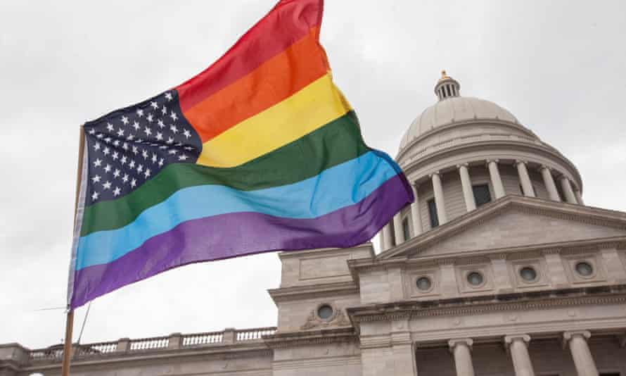 """A rainbow flag flies over the crowd during a press conference by the Human Rights Campaign on the steps of the Arkansas State Capital in Little Rock following Gov. Asa Hutchinson's comments on House Bill 1228, a bill passed which prohibits state and local governments from infringing on a person's religious beliefs without a """"compelling"""" interest,"""