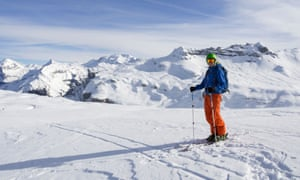 ale skier skiing in Le Grand Massif ski area with views to snowcapped mountains in the French Alps. Flaine, Rhone-Alpes,